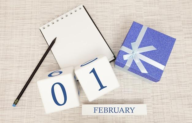 Kalender met trendy blauwe tekst en cijfers voor 1 februari en een geschenk in een doos.