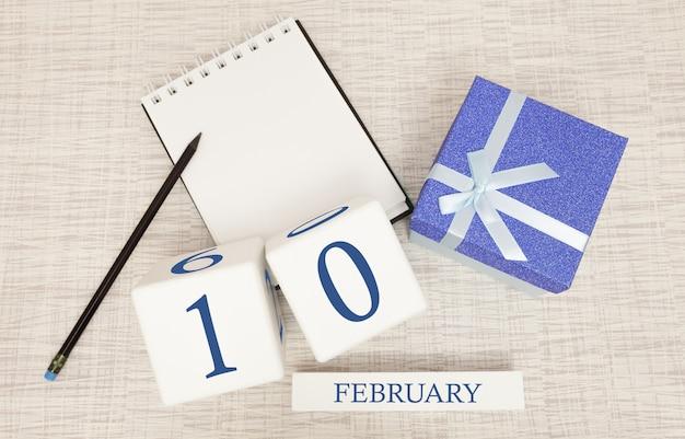 Kalender met trendy blauwe tekst en cijfers voor 10 februari en een geschenk in een doos.