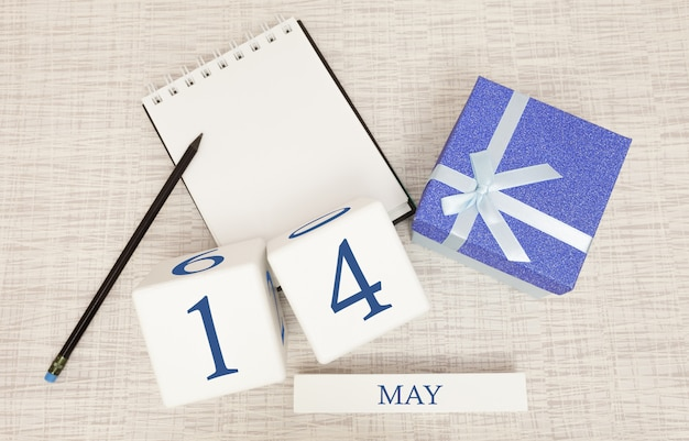 Kalender met trendy blauwe tekst en cijfers voor 14 mei en een geschenk in een doos.