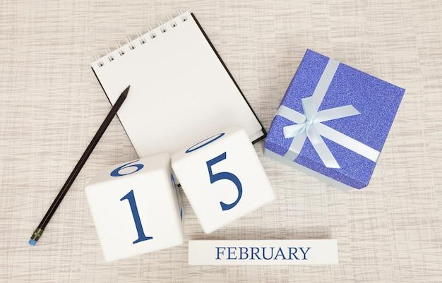 Kalender met trendy blauwe tekst en cijfers voor 15 februari en een geschenk in een doos.