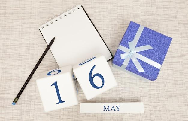 Kalender met trendy blauwe tekst en cijfers voor 16 mei en een geschenk in een doos.
