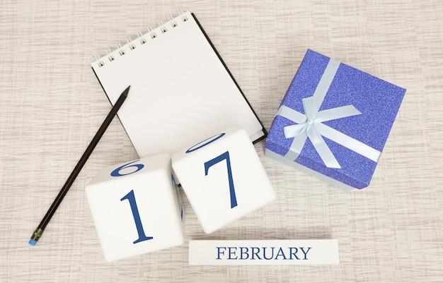 Kalender met trendy blauwe tekst en cijfers voor 17 februari en een geschenk in een doos.