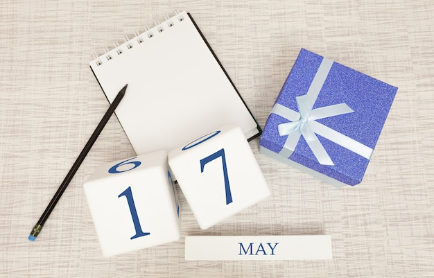 Kalender met trendy blauwe tekst en cijfers voor 17 mei en een geschenk in een doos.