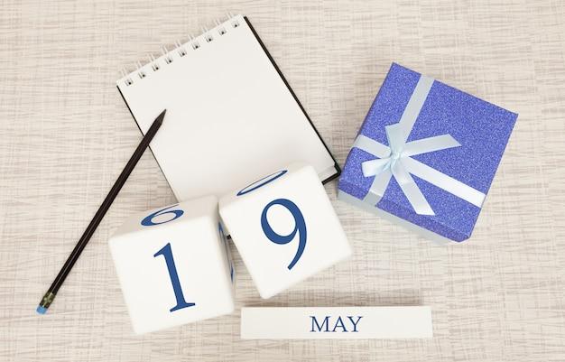Kalender met trendy blauwe tekst en cijfers voor 19 mei en een geschenk in een doos.