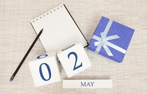 Kalender met trendy blauwe tekst en cijfers voor 2 mei en een geschenk in een doos.
