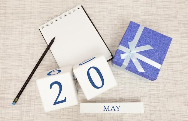 Kalender met trendy blauwe tekst en cijfers voor 20 mei en een geschenk in een doos.