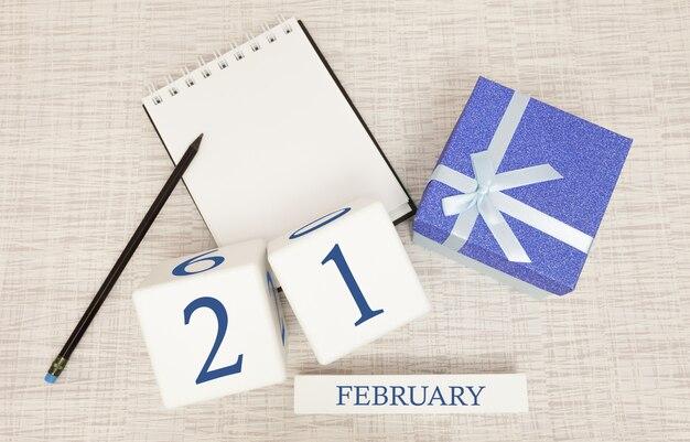 Kalender met trendy blauwe tekst en cijfers voor 21 februari en een geschenk in een doos.