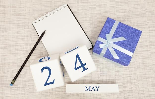 Kalender met trendy blauwe tekst en cijfers voor 24 mei en een geschenk in een doos.