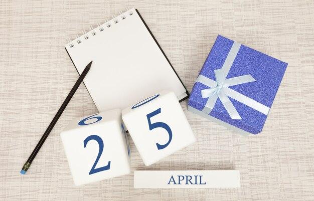 Kalender met trendy blauwe tekst en cijfers voor 25 april en een geschenk in een doos. Premium Foto