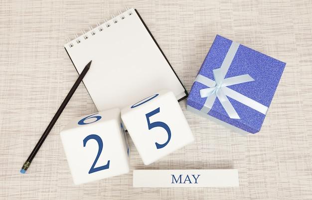 Kalender met trendy blauwe tekst en cijfers voor 25 mei en een geschenk in een doos.