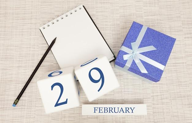 Kalender met trendy blauwe tekst en cijfers voor 29 februari en een geschenk in een doos.