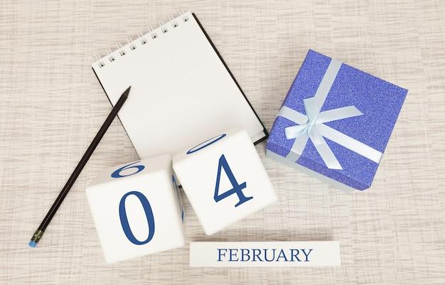 Kalender met trendy blauwe tekst en cijfers voor 4 februari en een geschenk in een doos.