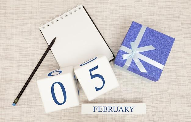 Kalender met trendy blauwe tekst en cijfers voor 5 februari en een geschenk in een doos.