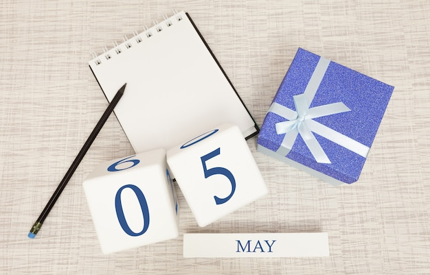 Kalender met trendy blauwe tekst en cijfers voor 5 mei en een geschenk in een doos.