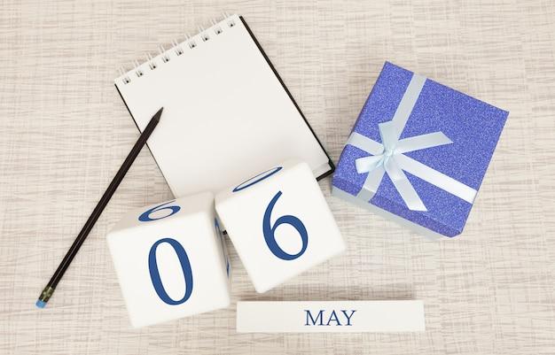 Kalender met trendy blauwe tekst en cijfers voor 6 mei en een geschenk in een doos.