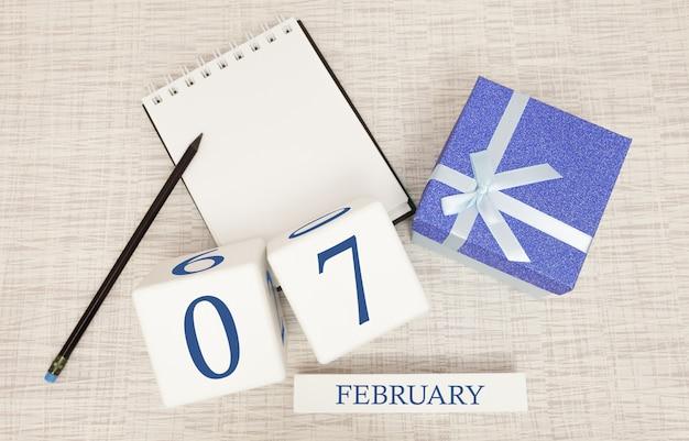 Kalender met trendy blauwe tekst en cijfers voor 7 februari en een geschenk in een doos.