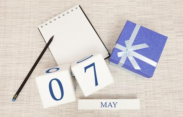 Kalender met trendy blauwe tekst en cijfers voor 7 mei en een geschenk in een doos.