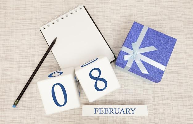 Kalender met trendy blauwe tekst en cijfers voor 8 februari en een geschenk in een doos.