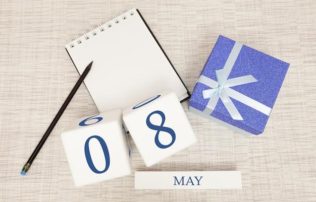 Kalender met trendy blauwe tekst en cijfers voor 8 mei en een geschenk in een doos.