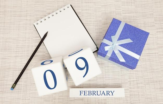 Kalender met trendy blauwe tekst en cijfers voor 9 februari en een geschenk in een doos.