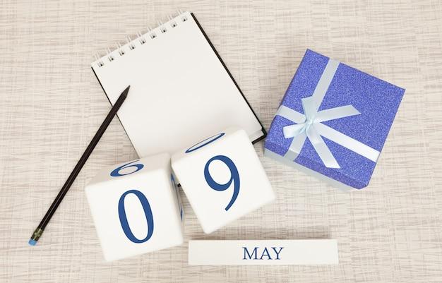 Kalender met trendy blauwe tekst en cijfers voor 9 mei en een geschenk in een doos.