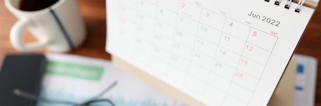 Kalender voor juni rekenmachine en kopje thee ligt op tafel. zakelijke taken plannen voor maandconcept