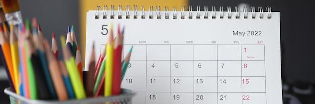 Kalender voor mei met kleurpotloden ligt op tafel. planningstaken voor maandconcept