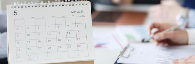Kalender voor mei staat op het bureaublad tegen de achtergrond van werknemers. zakelijke taken plannen voor maandconcept