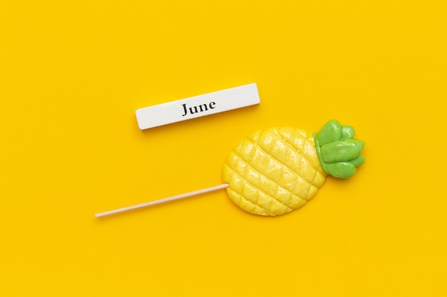 Kalender zomer maand juni, ananas lollipop op gele achtergrond.