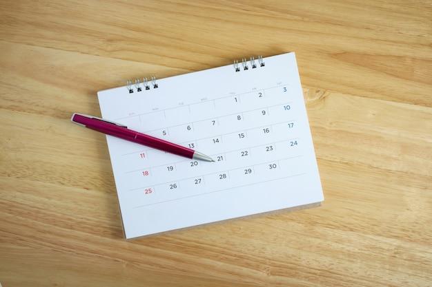 Kalenderpagina met pen op houten bureaulijst