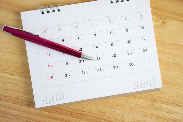 Kalenderpagina met pen op houten bureautafel