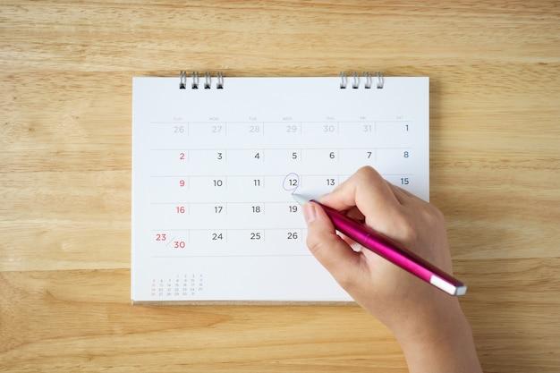 Kalenderpagina op tafel met vrouwelijke hand met pen, bovenaanzicht