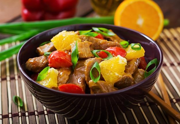 Kalfsfilet - roerbak met sinaasappels en paprika in zoetzure saus op een houten tafel.