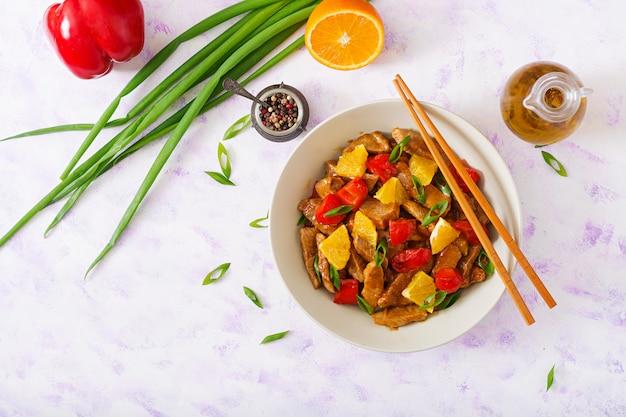 Kalfsfilet - roerbak met sinaasappels en paprika in zoetzure saus op een lichte tafel. plat liggen. bovenaanzicht