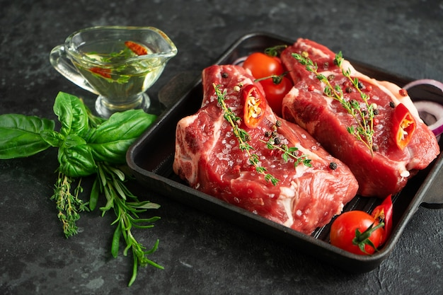 Kalfsvlees bot keu bal op grillpan met kruiden, kruiden en olijfolie op donkere achtergrond. selectieve aandacht