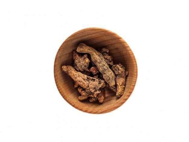 Kalganawortel in een houten kop op een witte lijst