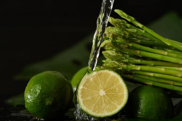 Kalk en asperges wassen met een stroom water, water uit de kraan op de groenten gieten close-up