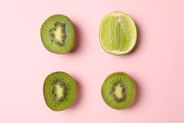 Kalk en avocado op roze achtergrond, ruimte voor tekst