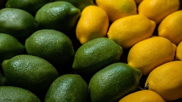 Kalk en citroenenachtergrond op marktteller. verse biologische citroen op een lokale boerenvoedselsupermarkt. close-up van fruit in de kartonnen doos op het schap van de supermarkt.