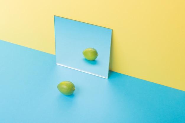 Kalk op blauwe tafel geïsoleerd op geel in de buurt van spiegel