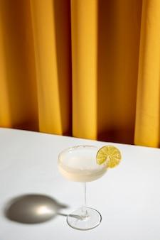 Kalkcocktail in een champagneschotel op wit bureau tegen geel gordijn