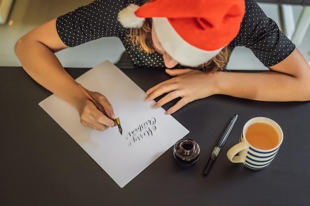 Kalligraaf jonge vrouw schrijft zin op wit papier