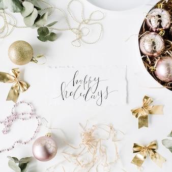 Kalligrafie woorden fijne feestdagen en frame gemaakt van kerstversiering met kerstballen, klatergoud, boog, eucalyptus.