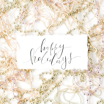 Kalligrafie woorden fijne feestdagen en kerstversiering klatergoud.