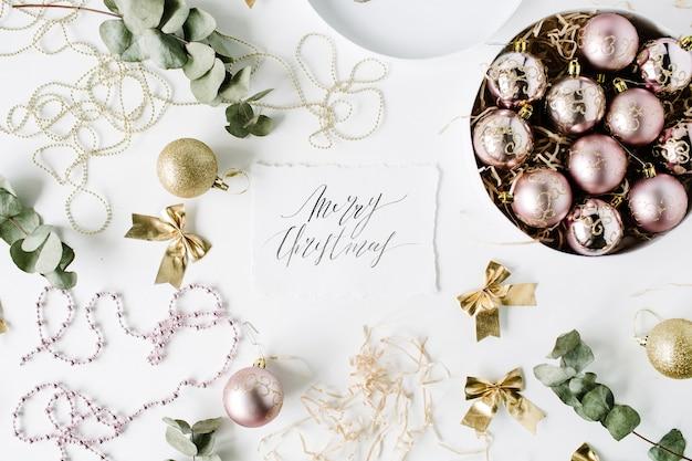Kalligrafie woorden vrolijk kerstfeest en frame gemaakt van kerstversiering met kerstballen, klatergoud, boog, eucalyptus.
