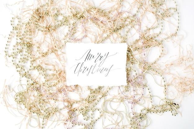 Kalligrafie woorden vrolijk kerstfeest en kerstversiering klatergoud.