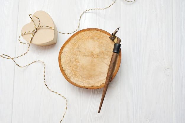 Kalligrafische veer op een houten cirkel met een hartdoos