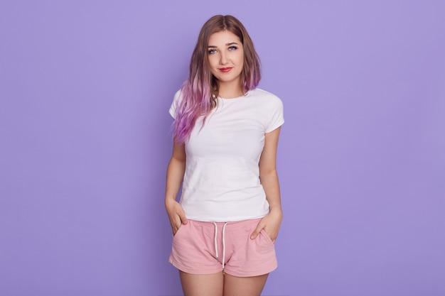 Kalm, aangenaam ogende vrouw met lila haar, gekleed in een wit t-shirt en roze korte handen in de zak met schattige uitdrukking, poseren geïsoleerd over paarse muur.