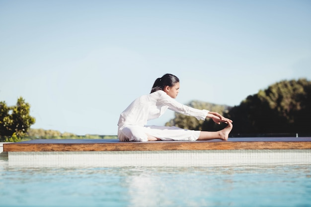 Kalm brunette doet yoga bij het zwembad