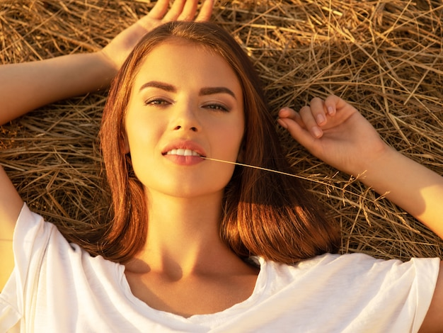 Kalm de jonge vrouw ontspant op de hooiberg.